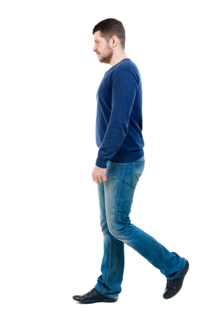 treading: Back view of going handsome man. walking young guy . bearded man in blue pullover passes by the viewer.