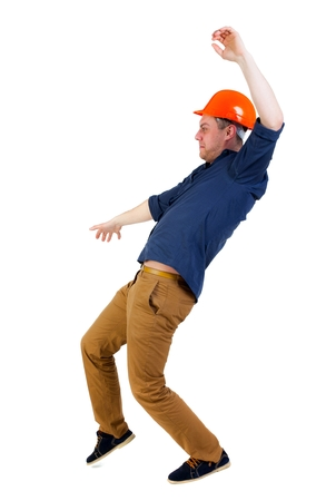 stumble: Balancing young man. or dodge the falling man. worker in construction helmet falls. Engineer in protective helmet falls slipping Stock Photo