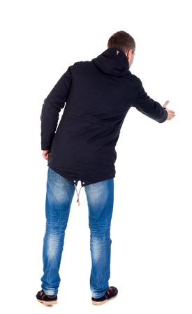 warm jacket: man in jacket holds out his hand for handshake. Isolated over white background. Guy greeted in a warm jacket. Stock Photo