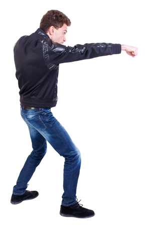 back view of guy funny fights waving his arms and legs. Curly guy in a black leather jacket stretched out his hand with his fist.