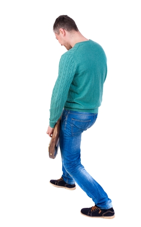 plucking: Back view of a young man with a guitar. man in a green jacket and blue jeans playing a guitar. Stock Photo