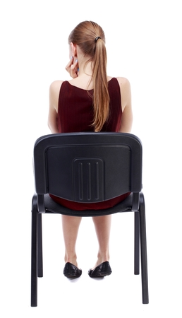 back view of young beautiful woman sitting on chair. Isolated over white background. A girl in a burgundy dress sitting on a chair thoughtfully touching the chin.