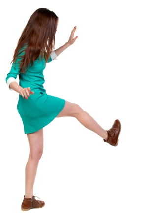 skinny woman funny fights waving his arms and legs. Long-haired brunette in a green dress kicks.