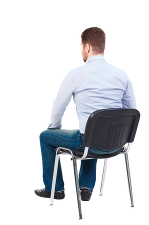 back view of business man sitting on chair. Bearded businessman in white shirt sits on a chair and looking forward. Stock Photo