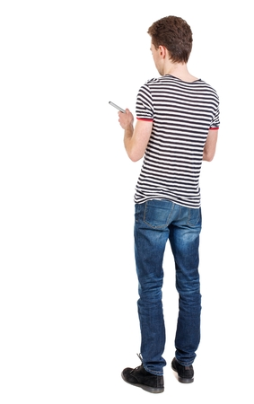 striped vest: back view of writing business man. Curly boy in a striped vest holding a pen in his hand. Stock Photo