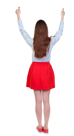 Back view of woman thumbs up. Rear view people collection. Isolated over white background. Long-haired brunette in red skirt lifted thumbs up.