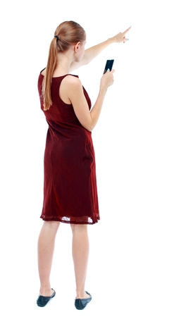 back view of pointing young beautiful girl with tablet computer. girl watching. girl in a burgundy dress sleeveless photographs on the phone and showing thumb.