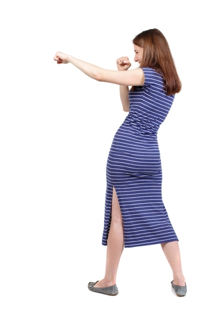 skinny woman funny fights waving his arms and legs. brunette in a blue striped dress stands sideways and hit a hand .. Stock Photo