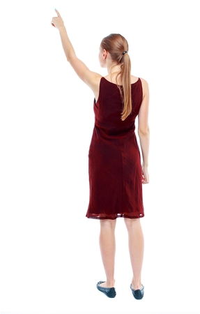 Back view of pointing woman. beautiful girl. Rear view people collection. girl in the maroon sleeveless dress shows a finger to the sky.