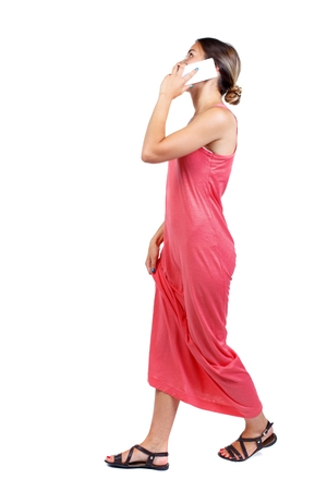 side view of a woman walking with a mobile phone. slender woman in a long red dress is talking and holding his hand dress.