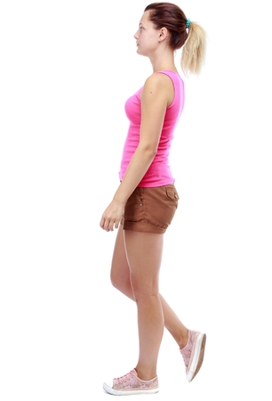 sadly: back view of walking woman . going gir in motion. Isolated over white background. Sport blond in brown shorts sadly passes.