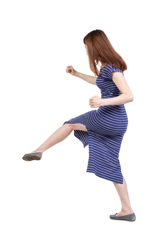 skinny woman funny fights waving his arms and legs. brunette in a blue striped dress beat someone down.
