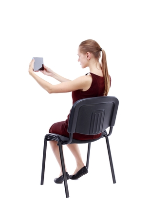 back view of woman sitting on chair and looks at the screen of the tablet. Isolated over white background. A girl in a burgundy dress sitting on a chair and taking pictures Tablet.
