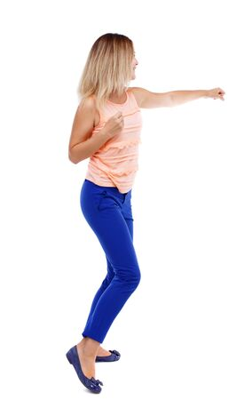 back view of standing girl pulling a rope from the top or cling to something. Isolated over white background. The blonde in a pink shirt punches. Stock Photo