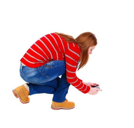 black and white photograph: back view of standing young beautiful woman using a mobile phone. blonde in a red striped sweater sitting photographing nothing on earth. Stock Photo