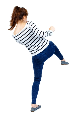 back view of woman funny fights waving his arms and legs. Rear view people collection. Girl in a striped sweater makes striking out kikbkosinga.