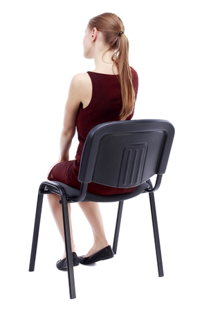 girl in burgundy dress: back view of young beautiful woman sitting on chair. Isolated over white background. A girl in a burgundy dress sitting on a chair listening to a lecture.