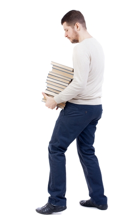 grasp: A man carries a heavy pile of books. back view. bearded man in a white warm sweater, tries to comfortably grasp the stack of books.