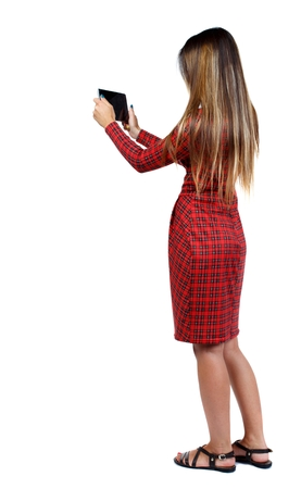 red plaid: back view of standing young beautiful woman and using a mobile phone. girl in red plaid dress stands sideways and pictures of the tablet. Stock Photo