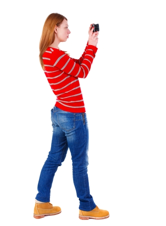 back view of standing young beautiful woman and using a mobile phone. Isolated over white background. The blonde in a red striped sweater is left side photographing compact camera.