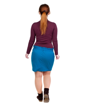 tied girl: back view of walking woman. beautiful blonde girl in motion. Girl with red hair tied in a pigtail goes deep into the frame. Stock Photo