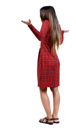 watching horror: Back view of angry young woman girl in red plaid dress throws his hands in surprise. Foto de archivo