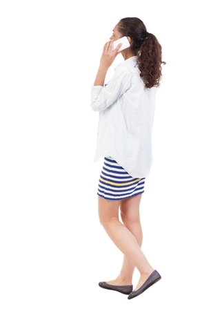 enthusiastically: a side view of a woman walking with a mobile phone. beautiful curly girl in motion.  backside view of person.  Rear view people collection. Isolated over white background.  African-African-American woman on the move enthusiastically talking on the phone Stock Photo