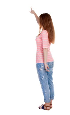 Back view of  pointing woman. beautiful redhaired  girl . girl shows something to someone. Rear view people collection.  backside view of person.  Isolated over white background. Girl in a white T-shirt points a finger at something interesting