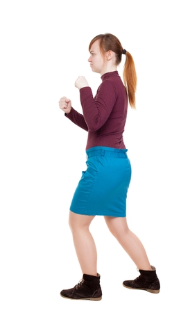 wimp: skinny woman funny fights waving his arms and legs. Rear view people collection.  backside view of person.  Isolated over white background. girl in a blue skirt and a burgundy sweater fights with fists.