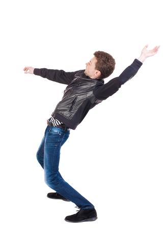 hombre cayendo: Equilibrio joven o esquivar la caída del hombre. Vista posterior recogida de las personas. trasero vista de la persona. Aislado sobre fondo blanco. El hombre sopla el viento. El chico de la chaqueta de cuero cae sobre su espalda. vista lateral. Foto de archivo