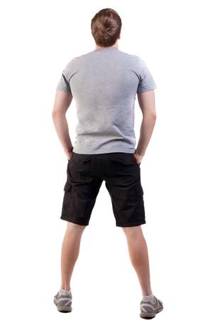 Hintere Ansicht des gutaussehenden Mannes im T-Shirt und in den kurzen Hosen . Lächelnder kleiner Tourist . Rückansicht Menschen zeigen . Rückansicht der Person . Isoliert über weißem Hintergrund