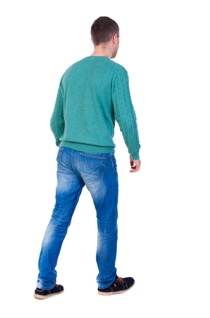 Back view of going handsome man. A man in a green jacket leaves left. Stock Photo