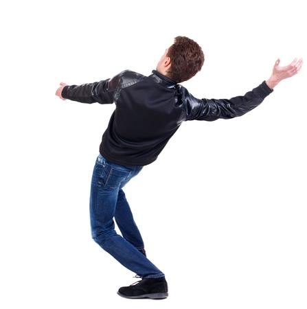 hombre cayendo: Equilibrio joven. o esquivar el hombre que cae. chico rizado en una chaqueta de cuero negro cae sobre su espalda.