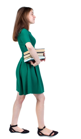 Girl comes with stack of books. side view. slender brunette in a green short dress is in the side with a pile of books.