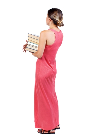 učebnice: Girl carries a heavy pile of books. back view. Rear view people collection. slender woman in a long red dress is standing with books in their hands.