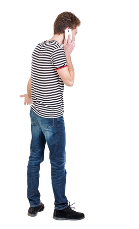 striped vest: back view of business man talking on mobile phone. Curly boy in a striped vest emotionally talking on the phone. Stock Photo