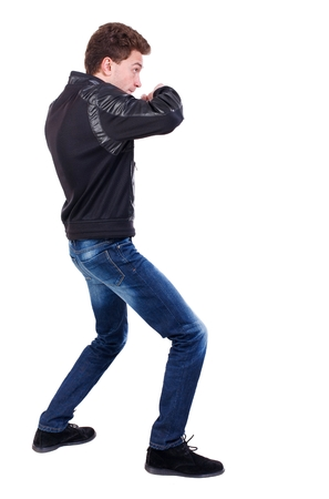 wimp: back view of guy funny fights waving his arms and legs. Curly guy in a black leather jacket fights waving his arms. Stock Photo