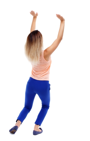 shove: back view of woman protects hands from what is falling from above. Isolated over white background. Blonde in blue pants shove something up