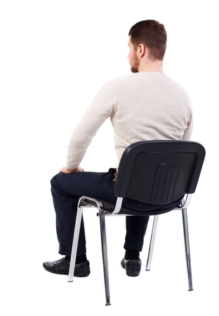 back view of business man sitting on chair. bearded man in a white warm sweater sits on a chair. Side view. Standard-Bild