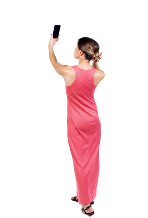 corrects: back view of standing young beautiful woman using a mobile phone. girl watching. slender woman in a long red dress corrects hair looking in the camera phone .. Stock Photo