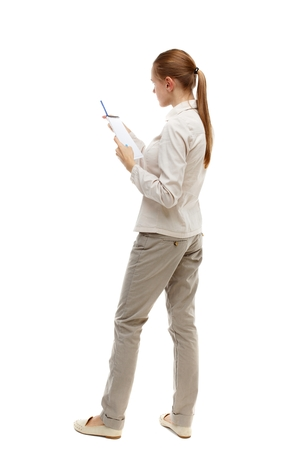 instructs: back view of stands woman takes notes in a notebook. Isolated over white background. Skinny girl in white denim suit instructs reading from a notebook. Stock Photo
