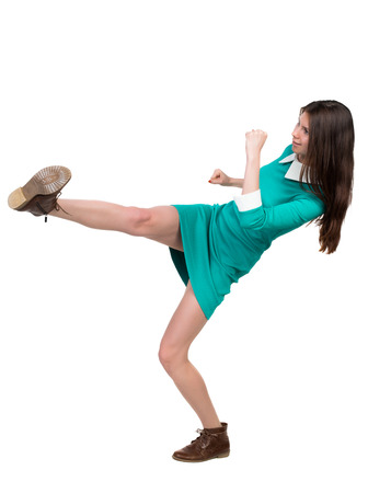 skinny woman funny fights waving his arms and legs. Isolated over white background. The girl in a green dress simply raised her left foot.