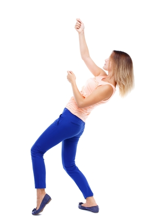 back view of standing girl pulling a rope from the top or cling to something. Isolated over white background. The blonde in a pink t-shirt hanging on a rope.
