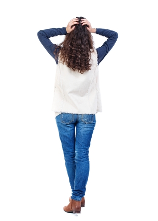 back view of standing young beautiful woman. Long-haired girl with curly hair in horror clutched at his head.
