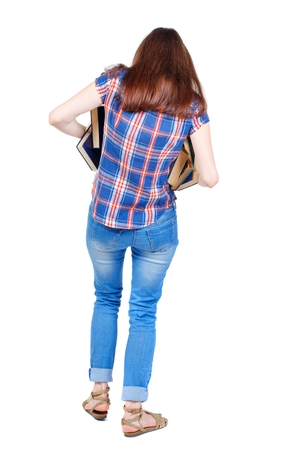 Girl comes with stack of books. back side view. Girl in a plaid shirt is trying to keep falling out of the book in his hands.