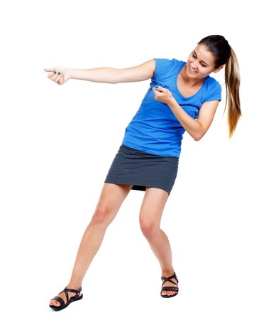 falda corta: back view of standing girl pulling a rope from the top or cling to something. girl watching. girl in a short skirt and a blue shirt pulling rope.