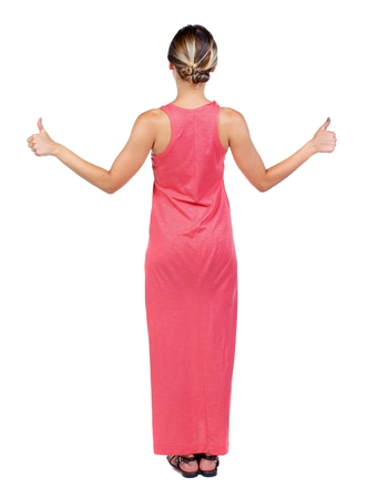 Back view of woman thumbs up. Rear view people collection. backside view of person. A slender woman in a long red dress showing a thumbs up with both hands. Stock Photo