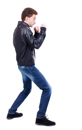 wimp: back view of guy funny fights waving his arms and legs. Curly guy in a black leather jacket in a fight.