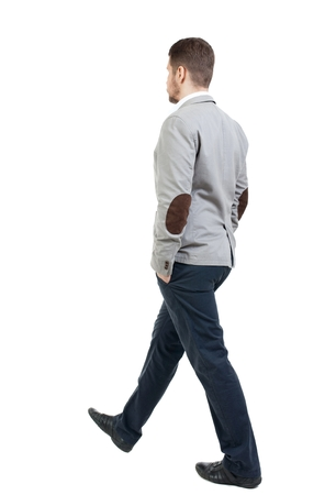 observes: Back view of walking businessman. bearded man in a gray jacket goes on a diagonal with his hands in his pockets. Stock Photo