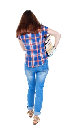 Girl comes with stack of books. back side view. Rear view people collection. Girl in a plaid shirt goes back to us holding books under his arm.